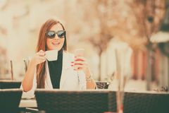 Woman using smart phone and drinking coffee. Young  happy business woman using smart phone and drinking coffee in street cafe Stock Photos