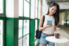 Woman using smart phone and enjoy her coffee in Hong Kong Royalty Free Stock Images