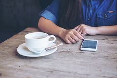 A woman using smart phone with feeling relax while sitting in vintage cafe with a coffee cup Royalty Free Stock Image