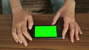 Woman using smart phone with green screen display. At home, close up shot of mobile phone with greenscreen on a table stock video footage