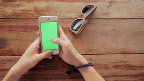 Woman using smart phone with green screen on wooden table background. Female hands scrolling pages, tapping on touch screen. top view. Office desk background stock video footage