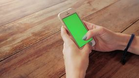 Woman using smart phone with green screen on wooden table background. Female hands scrolling pages, tapping on touch screen. top view. Office desk background stock footage