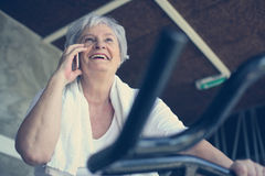 Woman using smart phone in the gym. Woman talking on the Royalty Free Stock Photos