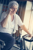 Woman using smart phone in the gym. Woman talking on the Royalty Free Stock Photo