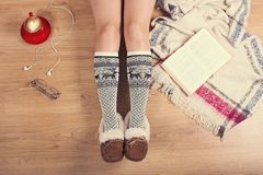 Woman sitting on the wooden floor with cup of coffee, phone, cookie and book. Close-up of female legs in warm socks with a deer vi stock photos