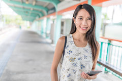 Woman using smart phone in light rail station at Hong Kong. Asian young woman Stock Images
