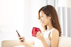 woman using smart phone in the living room royalty free stock photography
