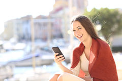 Woman using a smart phone and looking at camera Royalty Free Stock Photos