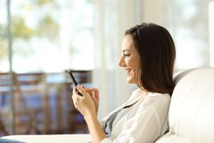 Woman using a smart phone in a luxury apartment. Side view portrait of a woman using a smart phone in a luxury apartment sitting on a sofa in the living room Stock Image