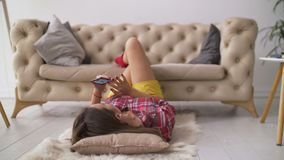 Woman using smart phone while lying on the floor stock footage