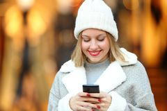 Woman using a smart phone in a mall in winter. Front view portrait of a happy woman using a smart phone in a mall in winter royalty free stock images