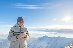 Woman using smart phone on the mountains. Panoramic view of snowcapped Alps in cold winter season. Concept of sharing life moments stock image