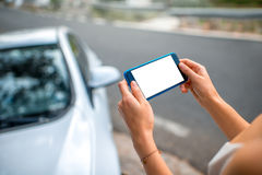 Woman using smart phone near the car Royalty Free Stock Photography