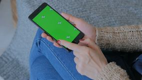 Woman using smart phone phone with green screen. Close up shot of woman`s hands with mobile phone stock footage