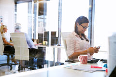 Woman using smart phone,phone at her desk in an office Stock Image