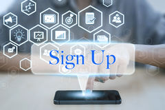 Woman using smart phone pressing button sign up icon. Stock Images