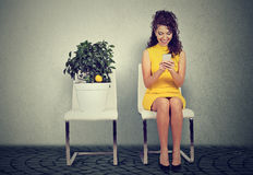 Woman using smart phone reading an email sitting on chair next to lemon tree. Young woman using smart phone writing reading an email sitting on chair next to Royalty Free Stock Photo