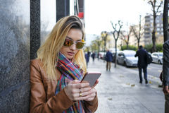 Woman using a smart phone in the street. Royalty Free Stock Photos