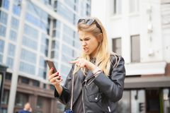 Blond Woman using a smart phone in the street in spring stock image