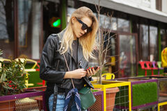 Woman using a smart phone in the street in spring Stock Photography