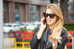 Woman using a smart phone in the street in spring Royalty Free Stock Photography