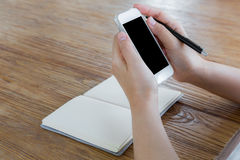 Woman using smart phone on the table Stock Images