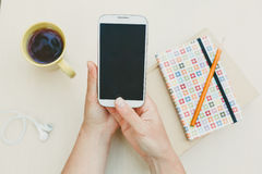 Woman using smart phone on the table Stock Photos