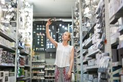 Woman using smart phone to take smart photo of items while buying led lights in hardware and furniture store. Young independent woman using smart phone to take royalty free stock photos