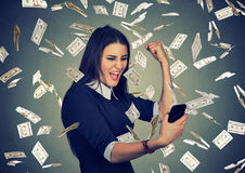 Woman using smart phone under money rain dollars falling down Stock Images