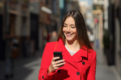 Woman using a smart phone while walk in the street. Happy woman using a smart phone while is walking in the street in a sunny day Stock Photos