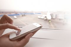Woman using smart phone by the window at aiport Stock Photography