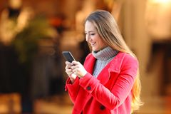 Woman using a smart phone in winter in a commercial centre. Happy woman using a smart phone in winter in a commercial centre in the street stock images