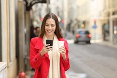 Woman using a smart phone in winter walking in the street. Portrait of a happy lady using a smart phone in winter walking in the street royalty free stock image