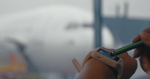 Woman using smart watch to type phone number. Close-up shot of a girl typing phone number on touchscreen smartwatch at the airport. Defocused plane and people in stock video
