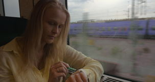 Woman using smart watch during train ride. Young blond woman sitting by the window in train and using smart watch with pen stock video footage