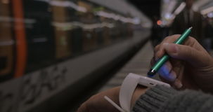Woman using smart watch at underground station. Close-up shot of a woman using smart watch in subway. She standing on the platform, train leaving the station stock video footage