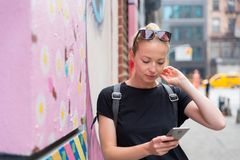 Woman using smartphone against colorful graffiti wall in New York city, USA. Closeup of female hipster with smart phone. Woman using smartphone against colorful stock photo