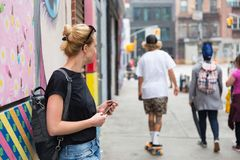 Woman using smartphone against colorful graffiti wall in New York city, USA. royalty free stock photography