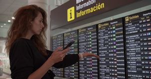 Barcelona, Spain - October 20, 2019: Woman using smartphone at airport. Young caucasian traveler checking boarding time stock video footage