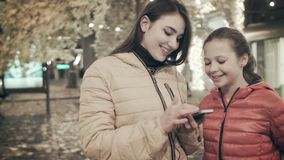 A woman is using a smartphone along with her daughter on a city street at night. Two girls use a smartphone in the fall stock footage