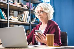 Attractive senior woman in eyeglasses using smartphone while sitting at desk with laptop and paper cup royalty free stock images