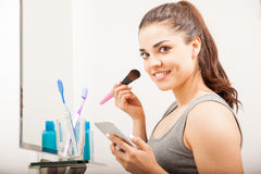 Woman using a smartphone in the bathroom Royalty Free Stock Photography