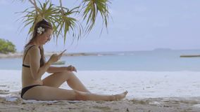 Woman using smartphone at beach drinking. Close up of woman holding. stock video