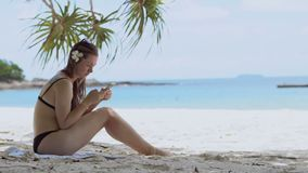 Woman using smartphone at beach drinking. Close up of woman holding. stock video footage