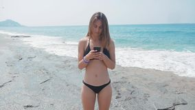 Young woman using smartphone on beach on summer travel vacation by sea. She is wearing bikini while relaxing during stock footage