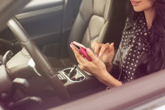 Woman using smartphone. Blurred car interior Royalty Free Stock Image