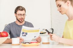 Woman using smartphone and boyfriend reading newspaper at table with coffee cups. And donuts royalty free stock photography