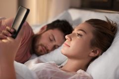 Woman using smartphone while boyfriend is sleeping royalty free stock images