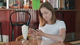 Woman using smartphone in cafe. In cafe on cruise ship stock footage