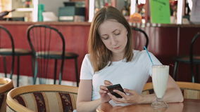 Woman using smartphone in cafe stock video